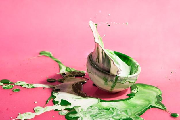 Zielony i biały farby pluśnięcie i filiżanka abstrakta tło