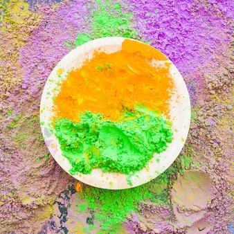 Zielony i pomarańczowy tradycyjny holi proszek na talerzu