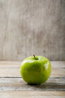 Zielony jabłczany boczny widok na grunge i lekkim drewnianym tle