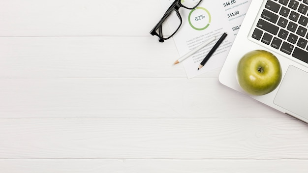 Zielony jabłko na laptopie z barwionymi ołówkami i eyeglasses na budżeta planie nad biurkiem