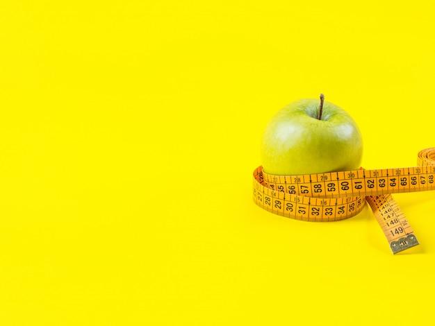 Zielony jabłko z pomiarową taśmą na kolorze żółtym