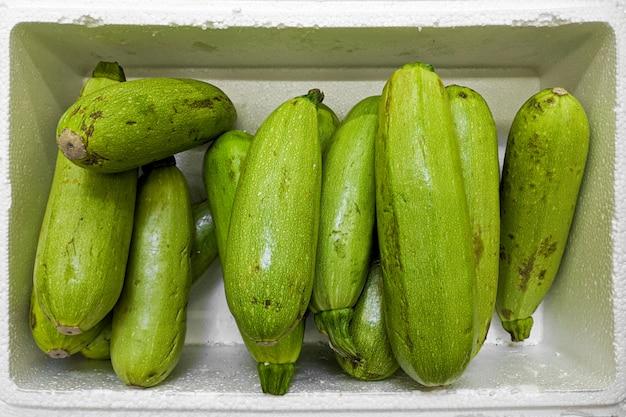 Zielony kabaczek. świeża odmiana do squasha uprawiana w sklepie.