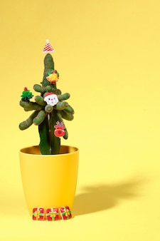 Zielony kaktus w żółtej doniczce ozdobiony małymi symbolami świątecznymi jako alternatywa świąteczna choinka na żółto z cieniem. hipster tropikalny koncepcja boże narodzenie. orientacja pionowa. miejsce na kopię.