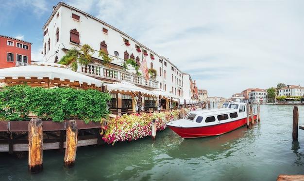 Zielony kanał wodny z gondolami i kolorowe fasady starych średniowiecznych budynków w słońcu w wenecji