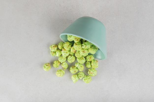 Zielony, kandyzowany popcorn rozsypany z małej miski na marmurowym stole.