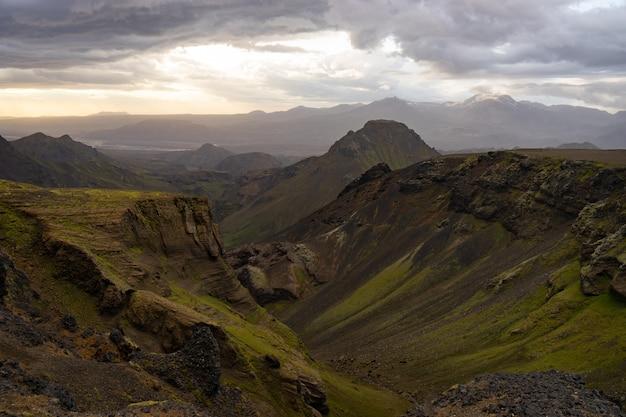 Zielony kanion i góry podczas dramatycznego i kolorowego zachodu słońca na szlaku turystycznym fimmvorduhals w pobliżu thorsmork.