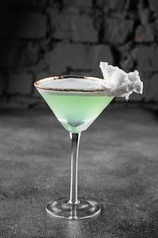 Zielony koktajl alkoholowy w szklance ozdobiony watą cukrową na szarej powierzchni.