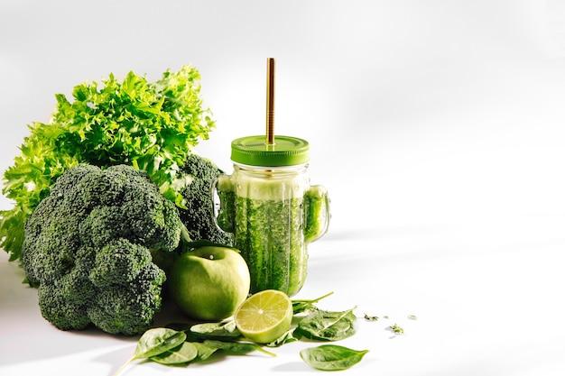 Zielony koktajl w kształcie słodkiego szklanego słoika kaktusa ze szpinakiem i zielonymi owocami i warzywami na białym stole. jedzenie wegetariańskie. koncepcja detoksykacji i diety.