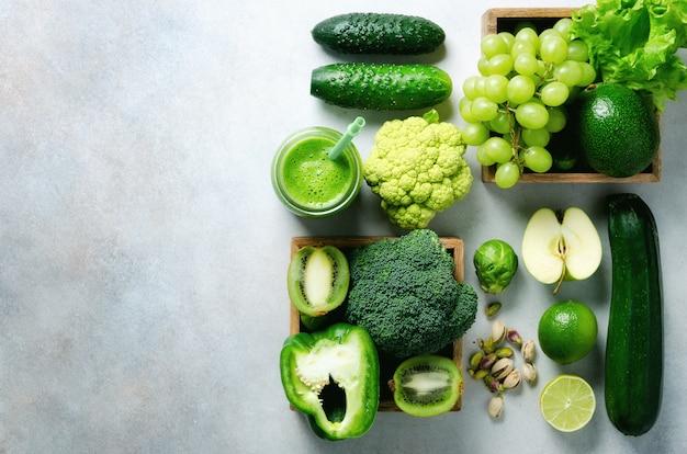Zielony koktajl w szklanym słoju ze świeżymi ekologicznymi warzywami i owocami na szaro. wiosenna dieta, zdrowa surowa wegetariańska, wegańska koncepcja, detox śniadanie, alkaliczne czyste jedzenie. skopiuj miejsce