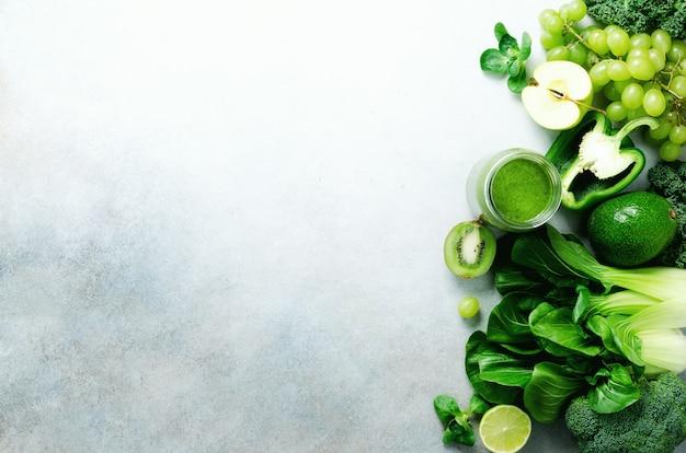 Zielony koktajl w szklanym słoju ze świeżymi ekologicznymi zielonymi warzywami i owocami na szaro