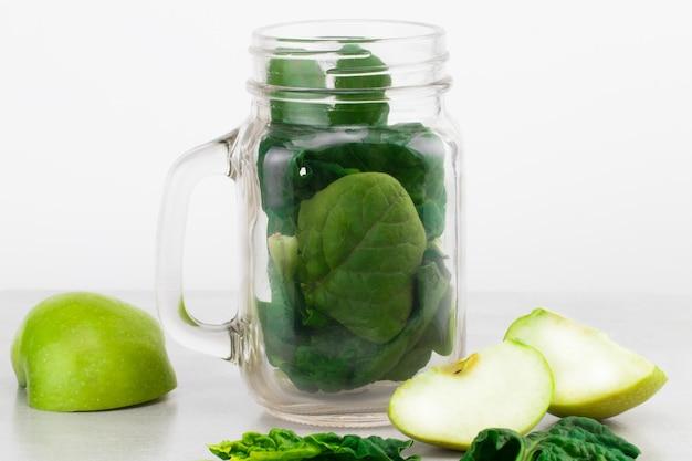 Zielony koktajl w szklanym słoju ze świeżymi ekologicznymi zielonymi warzywami i owocami na szarym tle. wiosenna dieta, zdrowe surowe wegetariańskie, koncepcja wegańska, śniadanie detoksykacyjne, alkaliczne, czyste jedzenie. skopiuj miejsce.