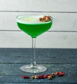 Zielony koktajl w szkle kryształowym przyozdobionym suszonymi pąkami róż