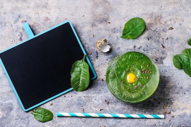 Zielony koktajl z jabłkiem i liśćmi na betonie