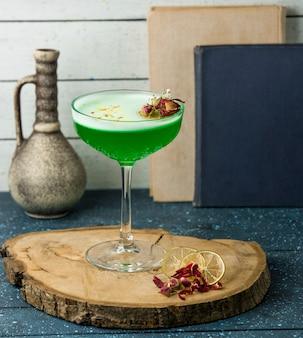 Zielony koktajl z kwiatami na stole