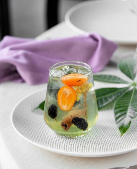 Zielony koktajl z owocami cytrusowymi i laską cynamonu.