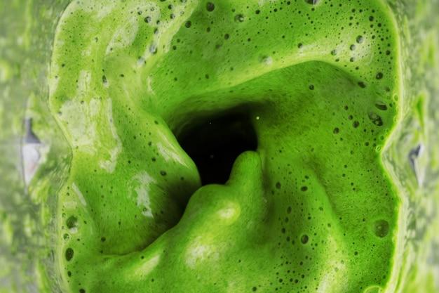 Zielony koktajl zdrowych warzyw i owoców zmieszany w blenderze, widok z góry