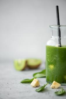 Zielony koktajl ze szpinaku, banana i kiwi z nasionami chia i małymi buteleczkami na szarym stole