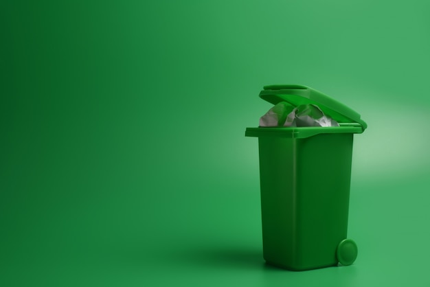 Zielony kosz na śmieci na zielonym tle. koncepcja ekologiczna.