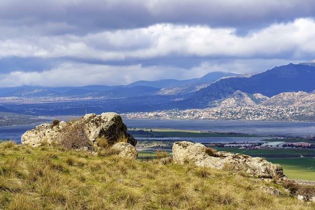 Zielony krajobraz z dużymi skałami, jeziorem i górami w tle i białymi chmurami na niebieskim niebie. navacerrada madrid. europa.