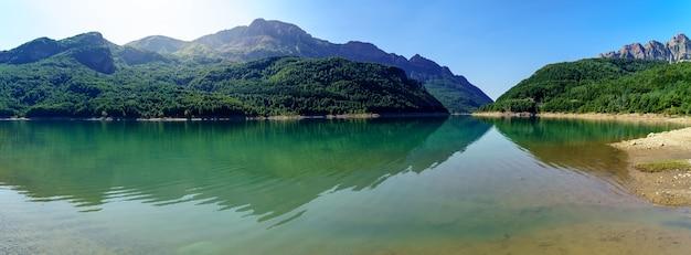 Zielony krajobraz z jeziorem i wysokimi górami, które odbijają się w wodzie, błękitnym niebie i blasku słońca. widok panoramiczny. pireneje, aragonia, hiszpania. europa.