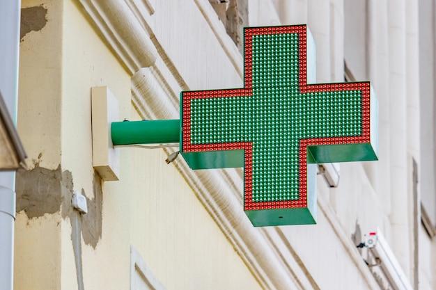 Zielony krzyż led zamontowany na ścianie nad wejściem do apteki