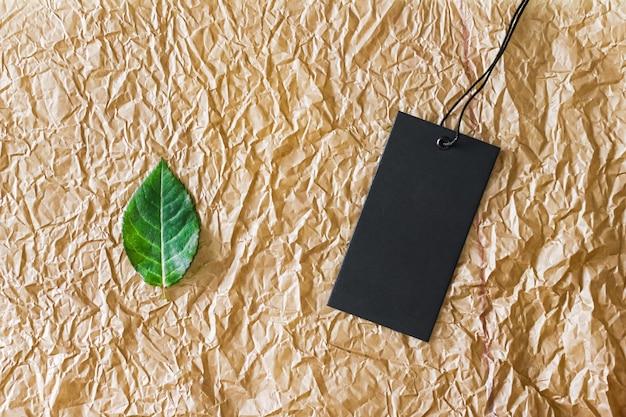 Zielony liść i czarna metka z ceną na materiale z recyklingu jako płaskie tło zrównoważona moda i br...