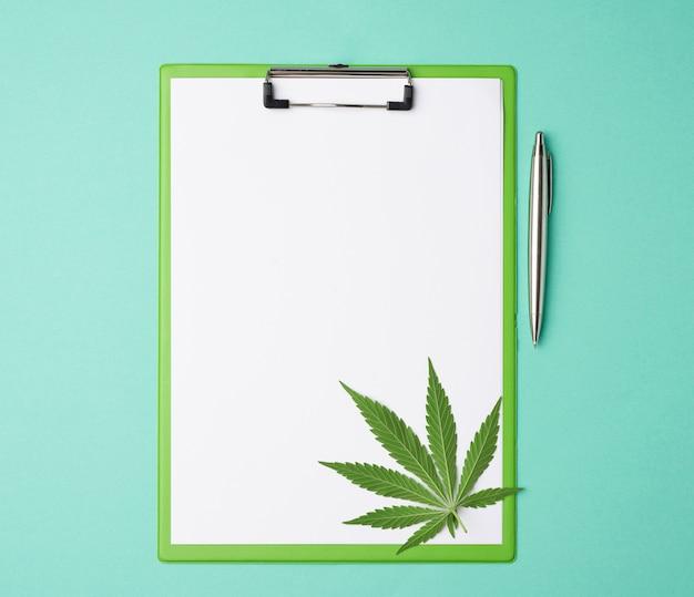 Zielony liść marihuany i uchwyt na dokumenty z pustymi białymi prześcieradłami