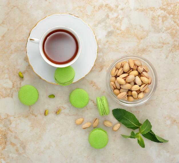 Zielony macaron z filiżanką herbaty