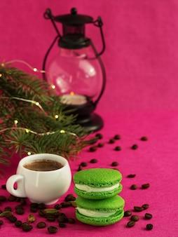 Zielony macaron z kremówką. w pobliżu znajduje się filiżanka espresso, palone ziarna kawy. gałąź choinki z girlandą i latarnią bożego narodzenia.