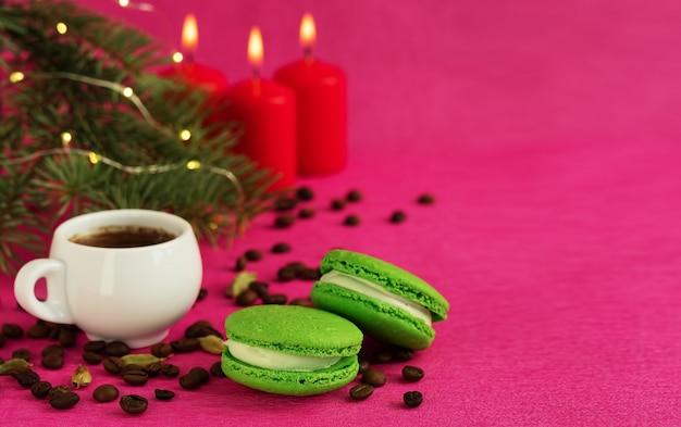 Zielony macaron z kremówką. w pobliżu znajduje się filiżanka espresso, palone ziarna kawy. gałąź choinki z girlandą i płonącymi świecami. makro, copyspace.