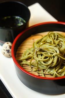 Zielony makaron na czarnej misce z jajkiem przepiórczym i sosem na białej tacy