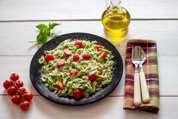 Zielony makaron z pomidorami i parmezanem. biały widok z góry.