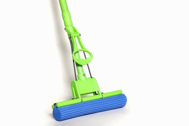 Zielony mop z niebieską ściereczką z mikrofibry na białym tle w zbliżeniu. widok z pierwszej osoby na mopy do sprzątania domu i czyszczenia podłogi. zaopatrzenie domu. koncepcja czyszczenia witryny. skopiuj miejsce