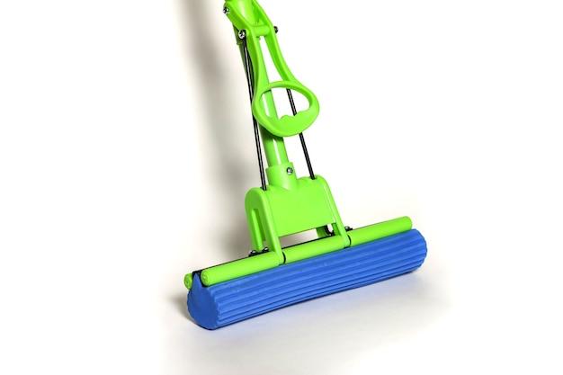 Zielony mop z niebieską ściereczką z mikrofibry na białym zbliżeniu. widok z pierwszej osoby na mopy do sprzątania domu i czyszczenia podłogi. artykuły domowe