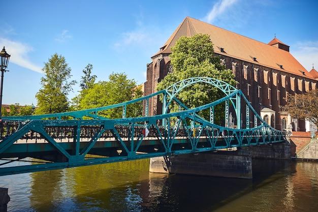 Zielony most ozdobiony wieloma miłosnymi zamkami i serduszkami we wrocławiu