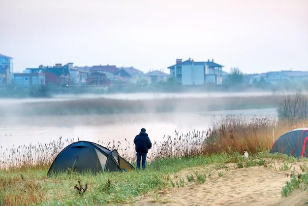 Zielony namiot i mężczyzna w pobliżu rzeki z poranną mgłą na wodzie. krajobraz podróży na świeżym powietrzu