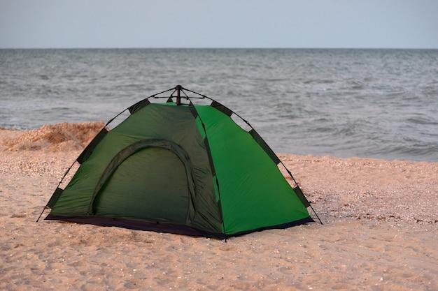 Zielony namiot kempingowy na plaży z morzem