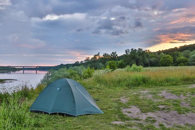 Zielony namiot turystyczny stoi nad brzegiem rzeki o zachodzie słońca