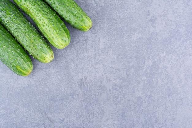 Zielony ogórek na białym tle na betonowej powierzchni