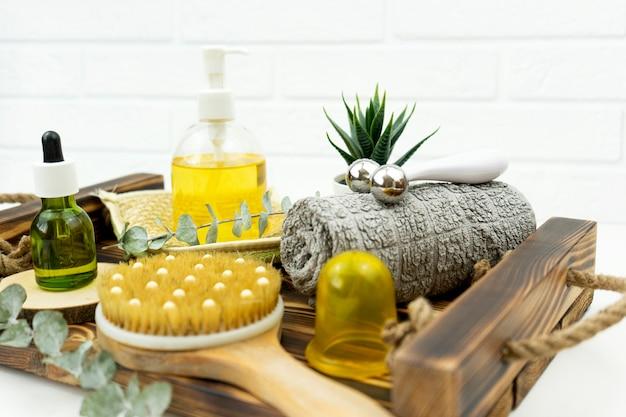 Zielony olejek cbd, wałek do twarzy, szczoteczka do masażu na sucho postaw na drewnianej tacy w łazience