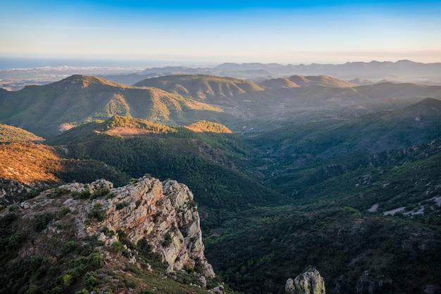 Zielony, pagórkowaty i kamienisty krajobraz wieczorem widziany z góry. śródziemnomorski krajobraz we wschodniej hiszpanii.