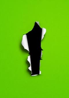 Zielony papier rozdarty na tle czarnej dziury