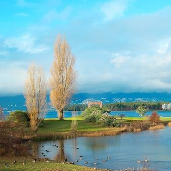 Zielony park w pobliżu morza z drapaczami chmur. vancouver, kanada.