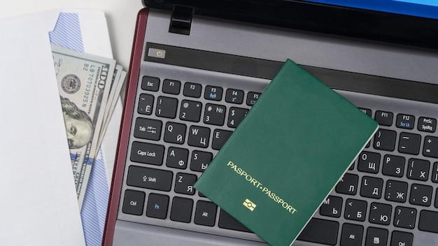 Zielony paszport z dolarami amerykańskimi na klawiaturze laptopa koncepcja przekupstwo i korupcja widok z góry