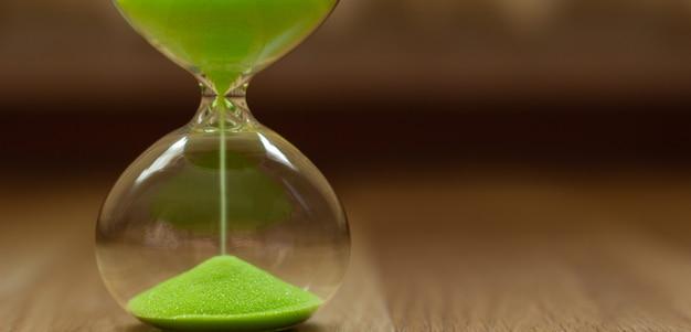 Zielony piasek w hourglass na zamazanym tle, zakończenie