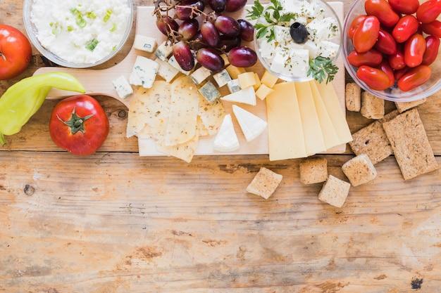 Zielony pieprz chili, pomidory, winogrona, chrupiący chleb i kostki sera na biurku