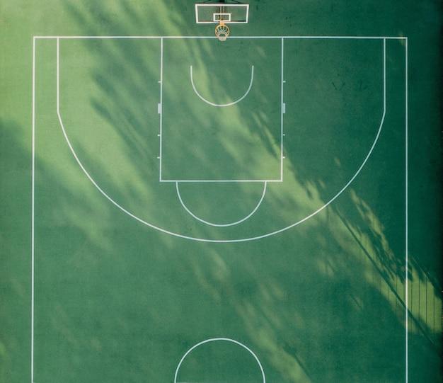 Zielony plac zabaw do koszykówki z białymi oznaczeniami i porannymi cieniami widok z góry