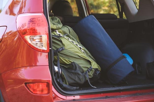 Zielony plecak i karemat w pokrowcu zapakowane do podróży w plener