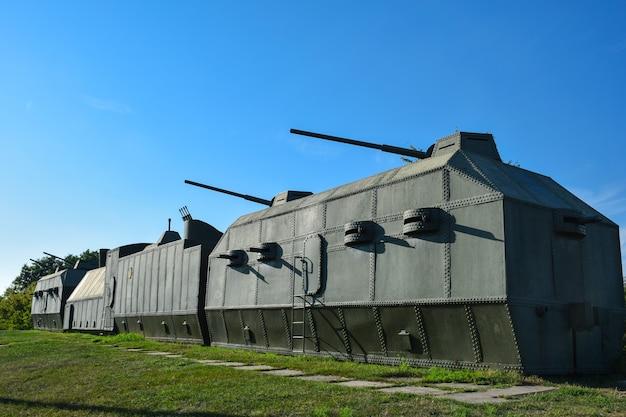 Zielony pociąg pancerny składający się z kilku wagonów z kilkoma działami i karabinami maszynowymi stoi na wzgórzu na tle błękitnego nieba