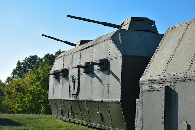 Zielony pociąg pancerny z kilkoma działami i karabinami maszynowymi stoi na wzgórzu na tle błękitnego nieba